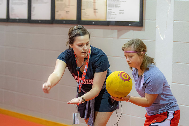 A student in the MS in Kinesiology graduate program working with a child on the University of Louisiana at Lafayette campus